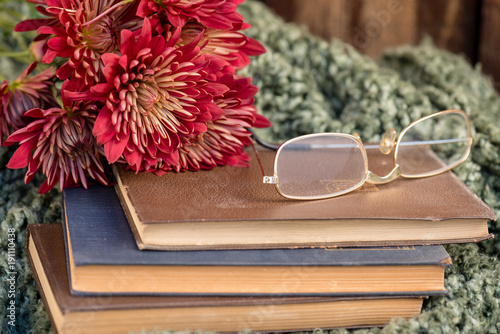 Close up of red mums next to a pair of wire rimmed glasses sitting on antique books and a knubby green knitted blanket.