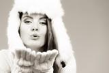 Woman wearing white furry hat sending air kisses. - 191113614