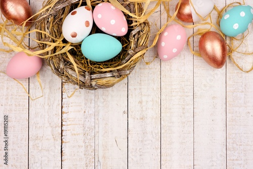 Springtime nest with pink, rose gold and turquoise painted Easter Eggs. Top border against a rustic white wood background.