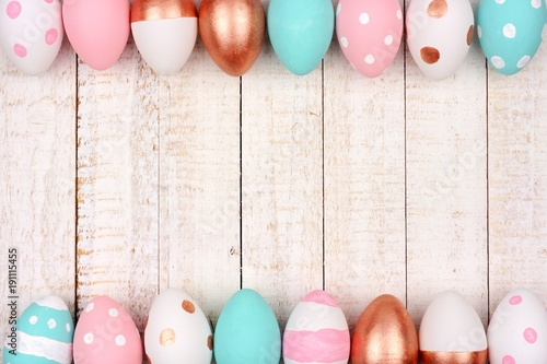 Easter egg double border. Rose gold, pink, turquoise and white colors on a white wood background.