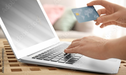 Fotobehang Hoogte schaal Woman holding credit card while using laptop, closeup. Internet shopping concept