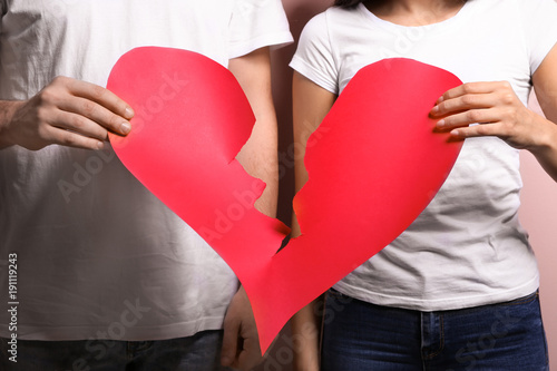 Couple tearing paper heart in half, closeup. Relationship problems