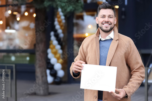 Fotobehang Hoogte schaal Business owner holding blank paper near his store