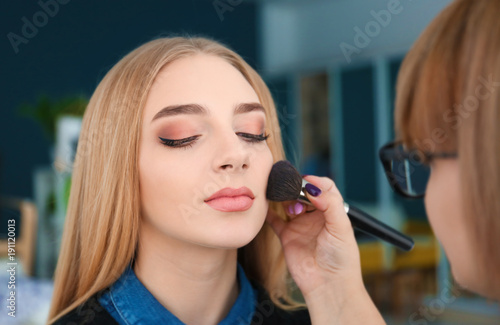 Professional visage artist applying makeup on woman's face backstage
