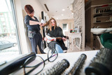 Hairdresser dries hair with a hairdryer in beauty salon - 191120221