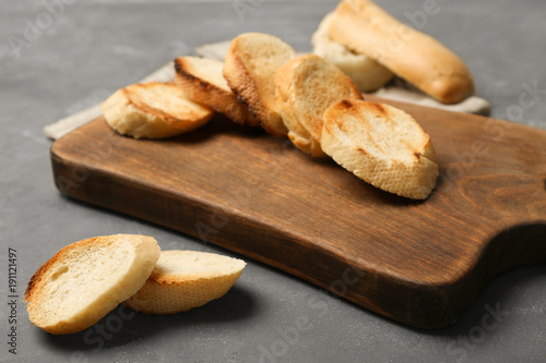Wooden board with toasted bread on grey background
