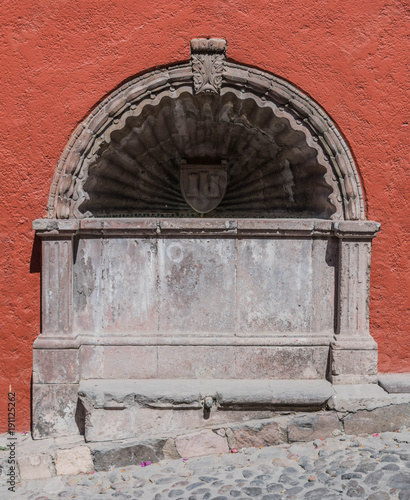 Beautiful, old, colorful stone water basin, fountain feature, with decorative elements, in San Miguel de Allende, Mexico