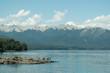Paisaje de lago con personas bañandose y montañas de fondo - 191137202