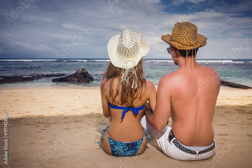 Portrait of happy couple, sitting at the beach, sea view.