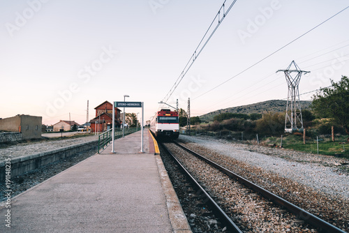 Tuinposter Spoorlijn Train at old railroad station platform in countryside at sunset