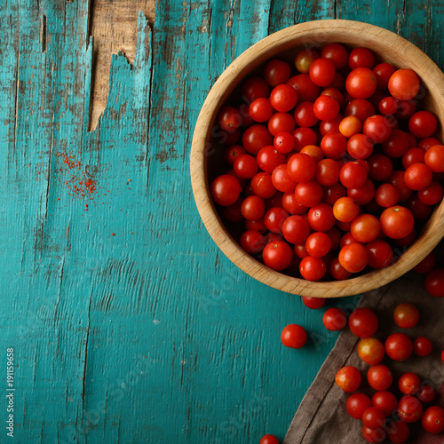 Fotobehang Kersen Raw organic tomatoes in wooden bowl