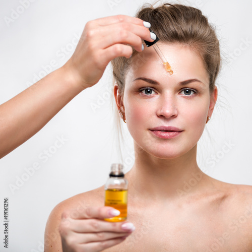 Portrait of a beautiful young woman with facial oil in hands
