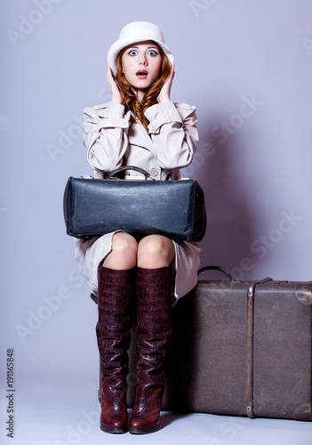 young redhead girl in cloak with suitcase