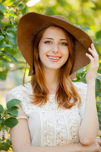 Young redhead girl in hat in apple tree garden