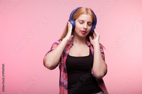 Fotobehang Muziek Young woman with her eyes closed listening to music on pink background in studio