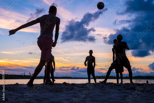 Unrecognizable sunset silhouettes playing football (soccer) on the beach