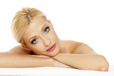Portrait of lying young beautiful blonde on white background