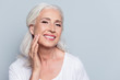 Leinwandbild Motiv Charming, pretty, old woman touching her perfect soft face skin with fingers, smiling at camera over gray background, using day, night face cream, cosmetology procedures