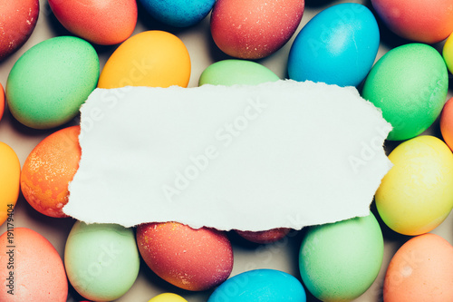 White paper laying on top of colorful eggs.