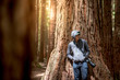 Young male photographer standing in Redwood forest