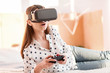 Interesting game. Amazed surprised elegant woman resting on bed while wearing VR glasses and using controller
