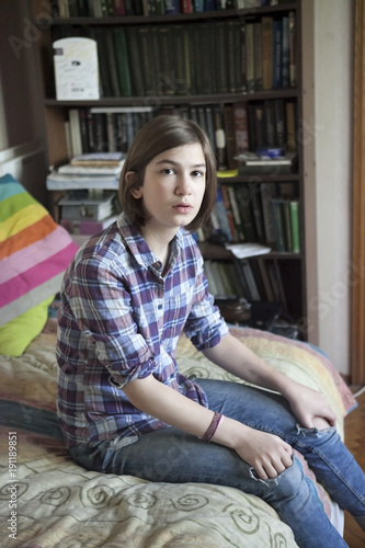 the A thoughtful girl in a plaid shirt is sitting on the bed in front of a bookcase