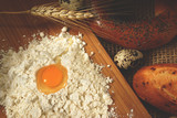 Broken quail egg in a hill of flour on a board before preparing a dough for buns - 191200047