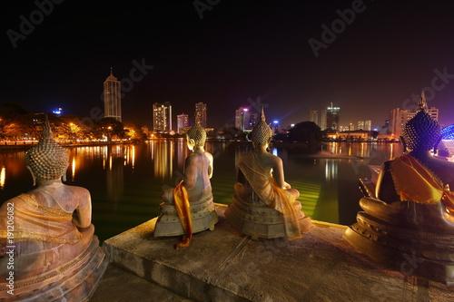 Fotobehang Boeddha Die Skyline von Colombo mit Spiegelung im See bei Nacht