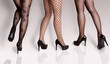 Three young woman, legs only in different elegant stylish pantyhose/ stockings. Studio shot, gray background