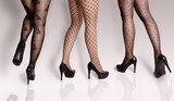 Three young woman, legs only in different elegant stylish pantyhose/ stockings. Studio shot, gray background  - 191206889