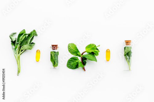Herbal medicine. Healing herbs in small bottles near pills on white background top view copy space