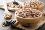 Uncooked assorted legumes in wooden bowl on wooden table - 191217845