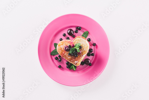top view of heart shaped pancake with berries and mint isolated on white, valentines day concept