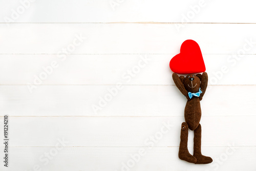 teddy bear with a heart in hands on a white background