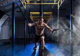 Man working out with battle ropes at gym - 191226474