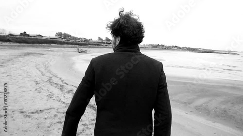 Angry man on beach in winter looking sad black and white