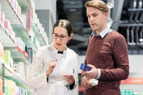 In de dag Apotheek Low-angle view of a handsome young man holding two prescribed medicines while looking at various pharmaceutical products in a modern drugstore with helpful pharmacists
