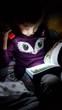 Bambina che legge al buio con una lampada - 191229646