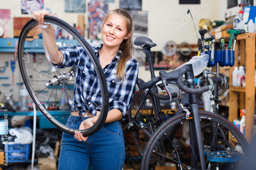 Female is replacing wheels of bicycle with another one in workshop.