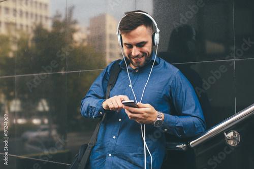 Fotobehang Muziek Handsome young man listen to music via smartphone and headphones on the street