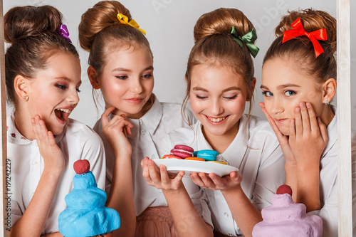 Aluminium Macarons Beautiful teenage model girls in pink tutu or tulle skirts with macaroons, fancy cakes and sweets in studio on white background