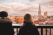 Two young tourist female friends looking at modern London skyline on day with clouds