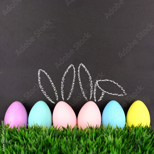 Row of Easter eggs in grass against a chalkboard background. Two with hand drawn Easter Bunny ears.