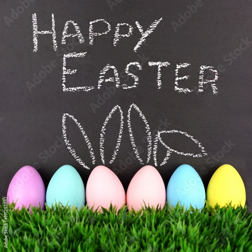 Happy Easter on chalkboard with row of Easter eggs in grass.Two with hand drawn Easter Bunny ears.