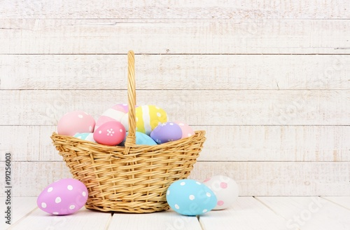 Easter basket filled with hand painted eggs over a rustic white wood background