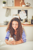 Smiling woman holding her cellphone in the kitchen. Smiling woman - 191258882