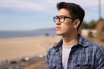 Young Asian man looking far away thinking