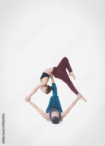 Plexiglas Fitness Young athletic couple practicing acroyoga. Balancing in pair