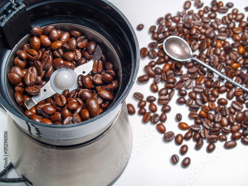 Fried black coffee beans lie in an electric coffee grinder ready for grinding close-up view from above