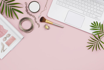 Online shopping concept with computer, pink background, catalog and products